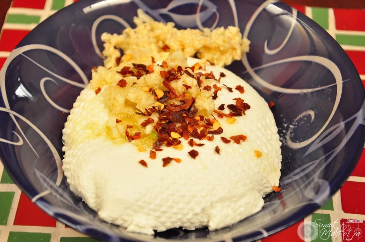 Homemade labneh recipe - labneh ready after being strained. Here see it being mixed with garlic and chili flakes