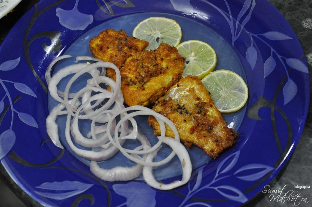 Serve Fried Fish Ajwaini with Lemon wedges and onion rings