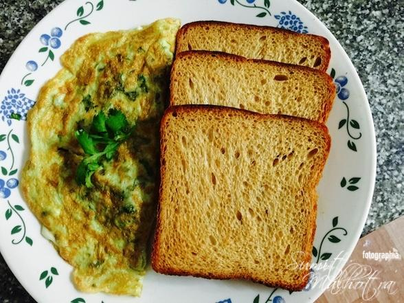 Enjoy cheese masala omelette with toasted brown bread
