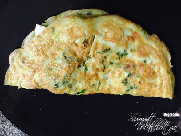 Fold Cheese Oregano Omelette in a nice half moon shape