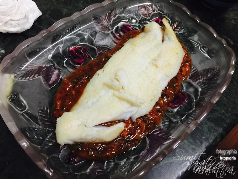 Lay the steamed basa fillet on the bed of sauce