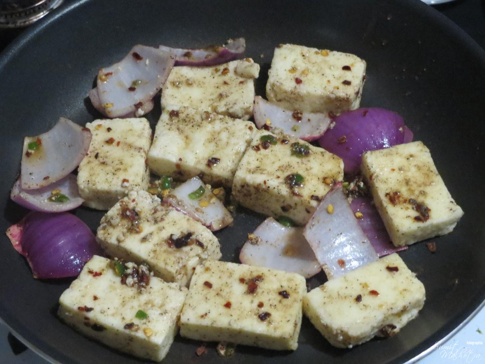 Heat a non-stick pan on medium flame, drizzle 1 tsp of olive oil and place the paneer and onion cubes on pan.