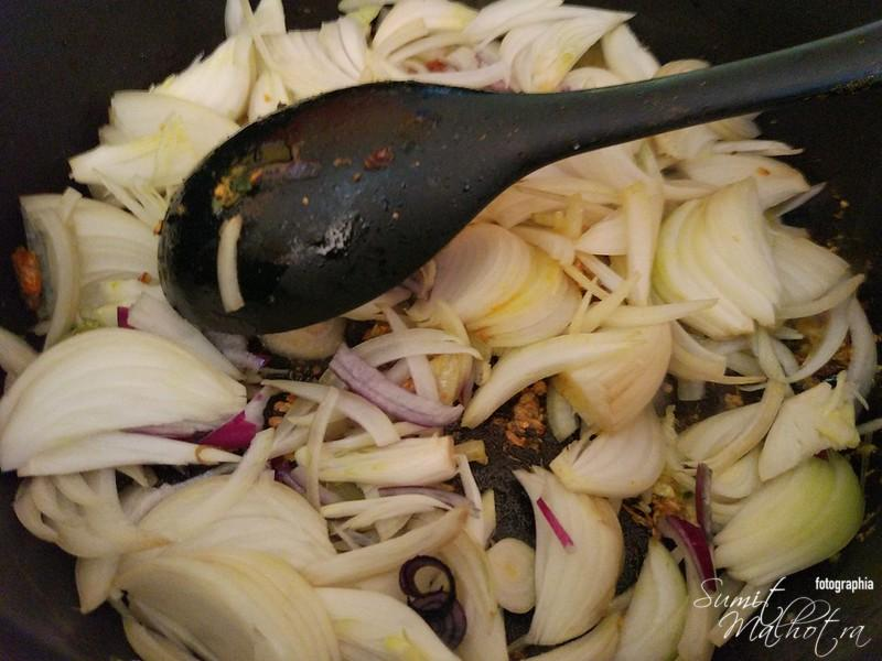 Add sliced red onions to a frying pan